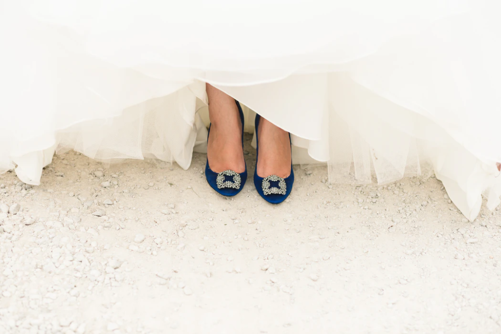 Royal blue pumps peeking out from under bridal gown